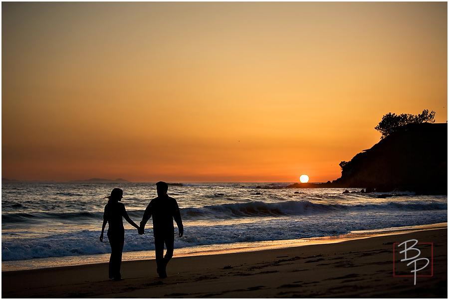 Taking a sunset stroll along Laguna Beach holding hands