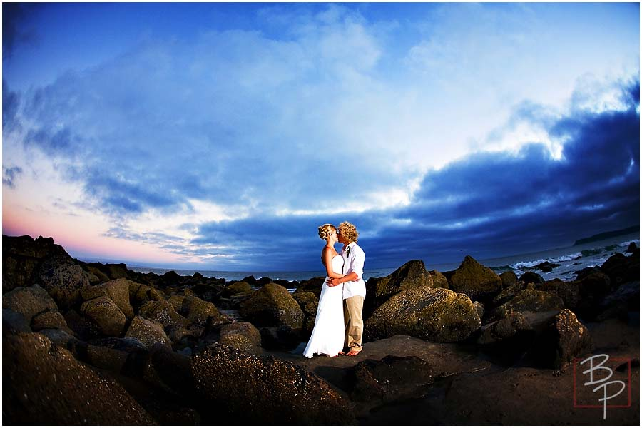Bride and groom under dramatic light at the beach
