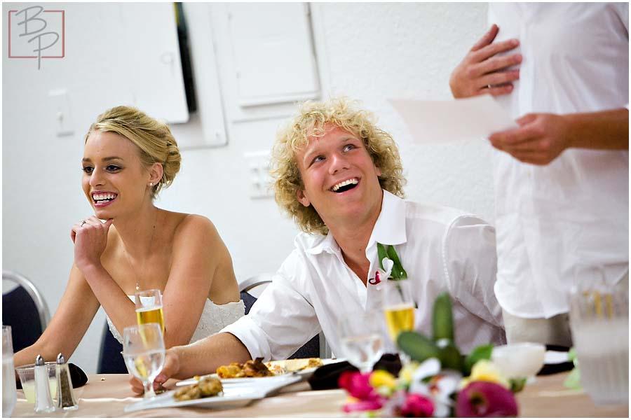 The bride and groom laughing at dinner