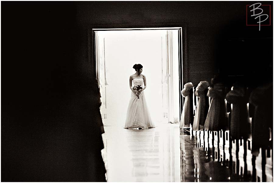 The bride silhouetted in the back of the church