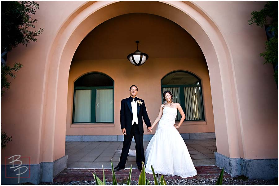 The bride and groom standing under an arch