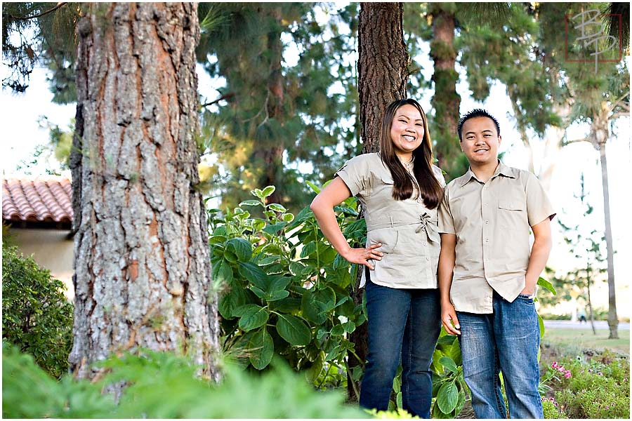 a couple standing next to a tree